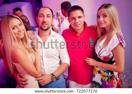 Odessa, Ukraine August 9, 2014: Ibiza night club. People smiling and posing on cam during concert in night club party. Man and woman have fun at club. Boy and girl at night club party