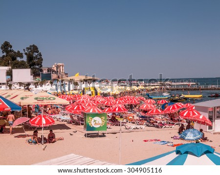 ODESSA, UKRAINE - August 10, 2013: Tourists sunbathe, swim and relax on beach having fun. Tourism is one of most important destinations in Europe. Hot summer. A good holiday season. Many tourists