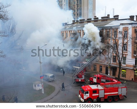 Odessa, Ukraine - December 29, 2016: A fire in apartment building. Strong bright light and clubs, smoke clouds window of their burning house. Firefighters extinguish fire in house. Work on fire stairs