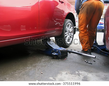 Odessa, Ukraine, February 10, 2016 -: Mechanic changing a punctured car tire on the road in the city. - stock photo