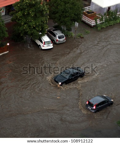 ODESSA, UKRAINE - JULY 16: Cars attempts to go along the street through flood waters after a heavy rain on July 16, 2012 in Odessa, Ukraine - stock photo