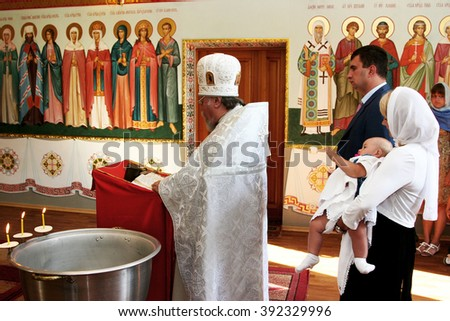 ODESSA, UKRAINE - July 23, 2009: Holy Orthodox rite of  sacrament of baptism  newborn baby in  small wooden Christian Church. Child Baptism in Church