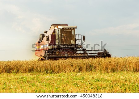 ODESSA, UKRAINE - July 11, 2016: The beginning of the harvest of ripe wheat. Modern harvester removes the ripe corn in field. Seasonal agricultural work, use of heavy specialized machinery on the farm