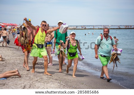 ODESSA, UKRAINE - June 9, 2015: Cheerful traders dried and smoked fish with a beer on the beach with tourists ryybu sell beer and shrimp. Petty trade on the open beach. Local popular services