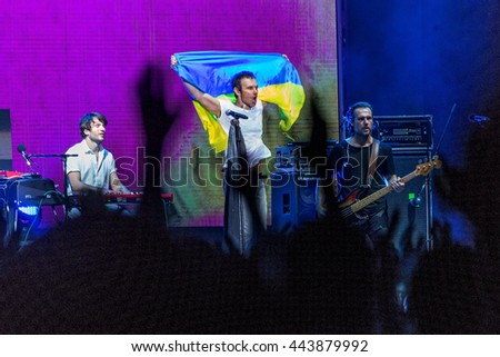 Odessa, Ukraine - June 25, 2016: Large crowd of spectators having fun at stadium, at concert of Ukrainian group Ocean Elzy during creative light and music show. Cheerful bright show in party club