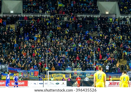 ODESSA, UKRAINE - March 24, 2016: Football fans and spectators in stands of  stadium emotionally support their team during match of national team of Ukraine and Cyprus. Emotions, torches, smoke, cries