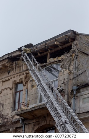 ODESSA, UKRAINE - MARCH 26, 2017: Rescuers on fire truck from fire staircase eliminate consequences of collapse of part of house as result of an earthquake.