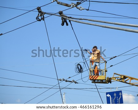 Odessa, Ukraine - May 22, 2016: Electricians at an altitude installs new cable high voltage against the blue sky.