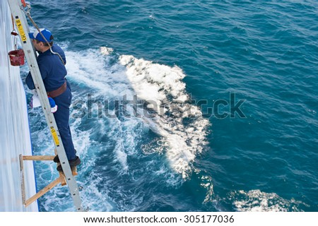 ODESSA, UKRAINE - MAY 19, 2015: Worker paint a hull of a ship in the sea.  - stock photo