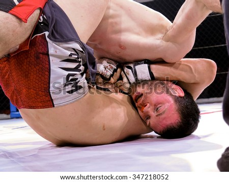 """Odessa, Ukraine - 24 November 2015: Athletes in the ring extreme Sport mixed martial arts competition tournament series  """"World MMA Network MAXMIX"""". The dramatic moment of battle punches - stock photo"""