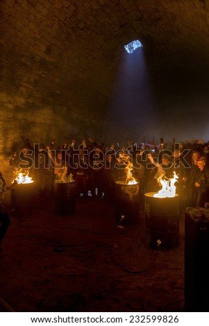 Odessa, Ukraine - November 22: Local rock band plays concert in underground catacombs dungeon destroyed building. A crowd of happy people, fans around campfire enjoy, November 22, 2014 Odessa, Ukraine