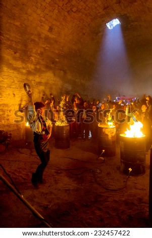 Odessa, Ukraine - November 22: Local rock band plays rock concert in underground catacombs dungeon destroyed building. A crowd happy people, fans campfire enjoy, November 22, 2014 Odessa, Ukraine