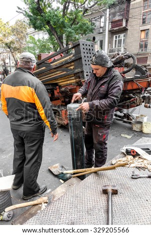 Odessa, Ukraine -October 18,2015: building technologies. Installation of plastic pipe by drilling point under highway. Pulling cable, pipe drilled  Stroebe. Modern complex laying of plastic pipes