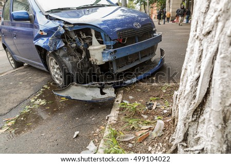 Odessa, Ukraine - October 14, 2016: Car during the day in the rain at high speed flew over the barrier of pedestrian crossing and crashed into standing tree. Car accident in city. Head-on collision
