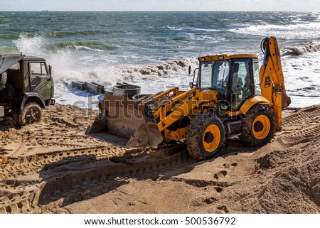ODESSA, UKRAINE -17 October 2016: Modern wheel loader backhoe makes earthworks for the construction of the urban beautification ukrepzony for the beach. Excavator digs sand on a sea beach