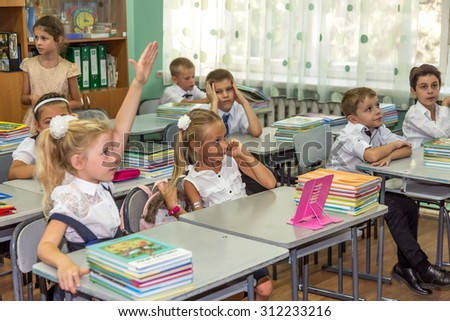 Odessa, Ukraine - September 1, 2015: elementary school students at their desks with textbooks on the first day of the school year. Feast Day of Knowledge. Beginning of a new academic year. - stock photo