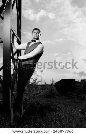 of a good looking beautiful young man in costume outdoors. Black - stock photo