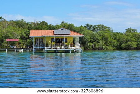 Off grid house over the sea with solar panels on the roof, Caribbean, Panama