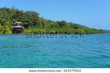 Off-grid oceanfront house and lush tropical vegetation on the coast of the Caribbean island of Bastimentos, Bocas del Toro, Panama, Central America - stock photo