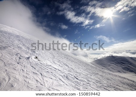 Off-piste ski slope and blue sky with sun. Georgia, ski resort Gudauri. Caucasus Mountains. Wide-angle view. - stock photo