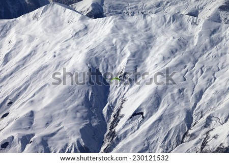 Off-piste slope and paraglider in nice day. Caucasus Mountains. Georgia, ski resort Gudauri. - stock photo