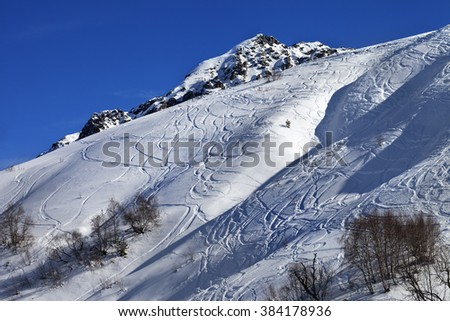 Off-piste slope with track from ski and snowboard on sunny day. Caucasus Mountains, Tetnuldi, Svaneti region of Georgia. - stock photo
