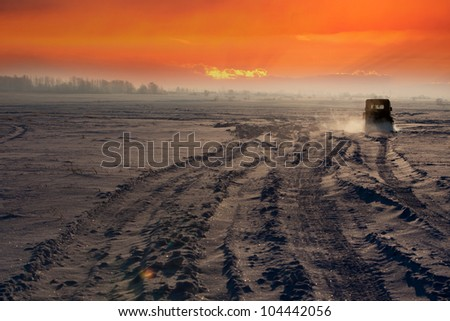 off-road car driving on the highway at sunset - stock photo