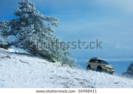 Off-road car on winter landscape - stock photo