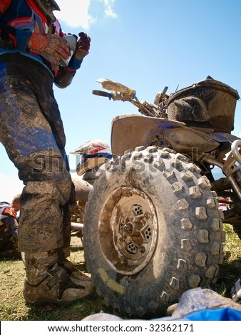Off-road dirt atv from low point against blue sky - stock photo