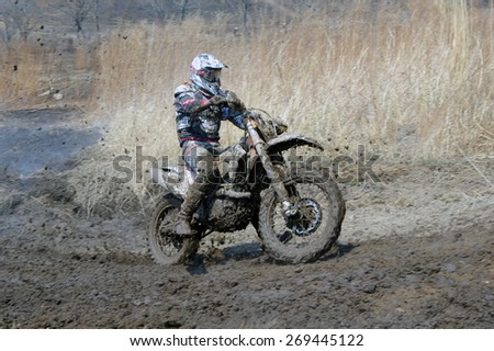 Off-road rider is jumping against a steaming ground   Nakhodka Russia 04.12.2015 - stock photo