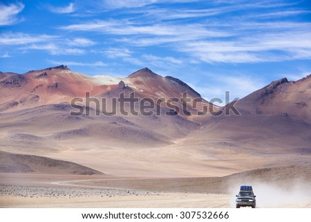 Off-road vehicle driving in the Atacama desert, Bolivia with majestic colored mountains and blue sky in Eduardo Avaroa Andean Fauna National Reserve, Bolivia - stock photo
