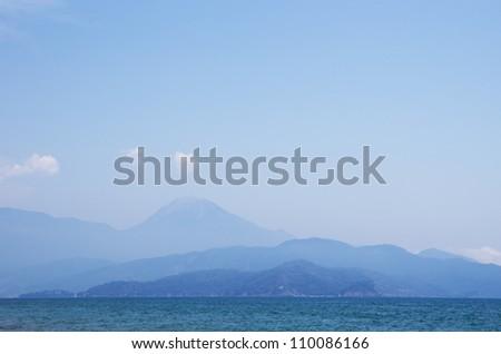 Off-shore mountains in haze - stock photo