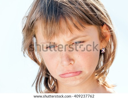 Offended face of young beautiful girl close-up on the background - stock photo