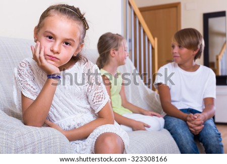 Offended little girl is jealous sister of teenage stepbrother in the living room - stock photo