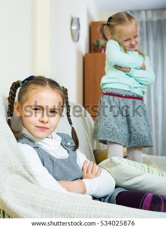 Offended little girl with pigtails sitting apart of sister after conflict at home