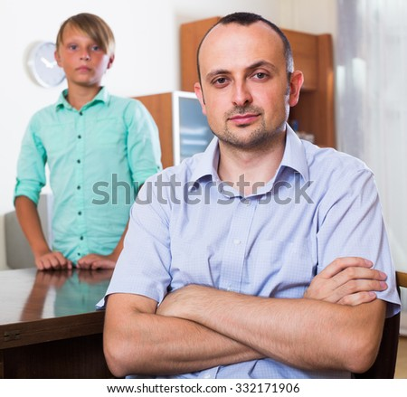 Offended man after arguing about problems  with teenage son - stock photo