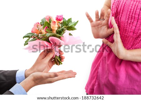 Offended woman and man with flowers for apology - stock photo