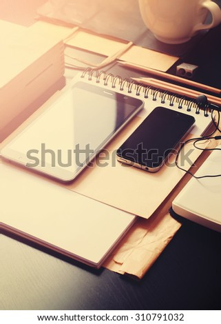 Office Accessories, Modern Devices Phone, Tablet, Pencils and Other Things on Black Table, selective focus, toned - stock photo