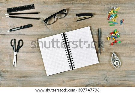 Office and school supplies over wooden desk background. Open book and writing tools. Retro style toned picture - stock photo