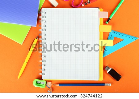 Office and student tools on orange background closeup - stock photo