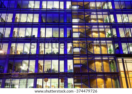 Office building exterior with people at work at night