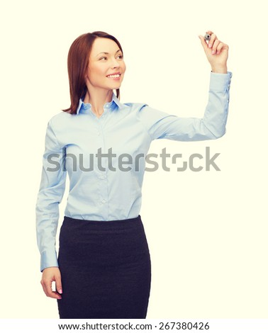 office, business and new technology concept - smiling businesswoman writing something in the air with marker - stock photo