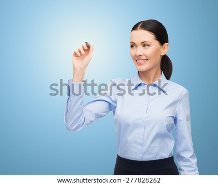 office, business, people and technology concept - businesswoman writing something in air with marker over blue background - stock photo