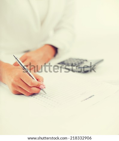 office, business, tax, accounting concept - businesswoman working with calculator in office