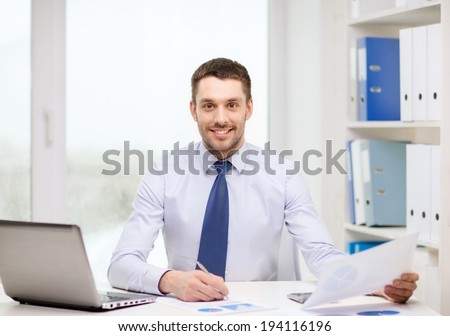 office, business, technology, finances and internet concept - smiling businessman with laptop computer and documents at office