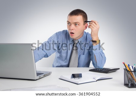 Office, business, technology, finances and internet concept - Surprised businessman with laptop computer and documents at office on gray background
