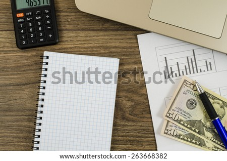 Office, business tools with notebook and dollar on wooden table - stock photo