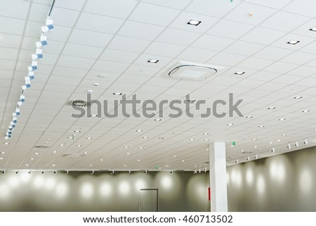 Office ceiling has modern light and the hatch for conditioning system ventilation.