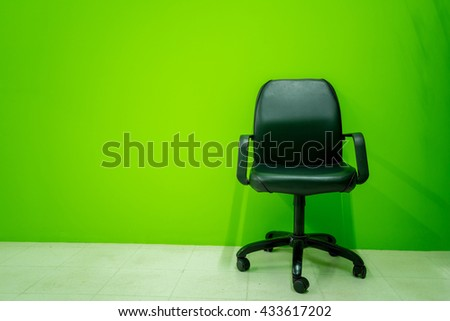 Office chair isolated on green wall - Business interior background and copy space   - stock photo