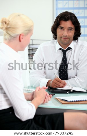 Office colleagues talking at a desk - stock photo